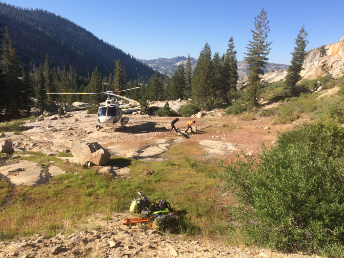 Sequoia staff disembarking a helicopter to start work in the Sierras.
